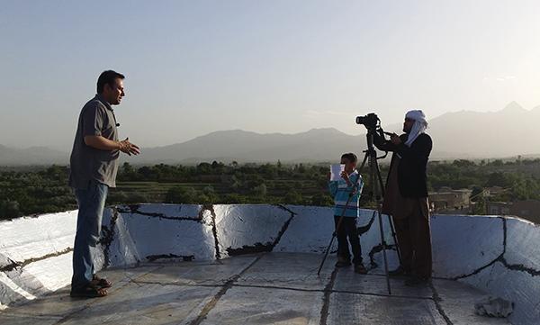 الصحفي الأفغاني ذبيح الله تمنى، على اليسار، يبث من خارج كابول في مايو/ايار عام 2015. وقتل تمنى والمراسل الأمريكي ديفيد جيلكي في عام 2016 بينما كانا يعملان مع راديو إن بي آر (ا ف ب / برويز سابون)
