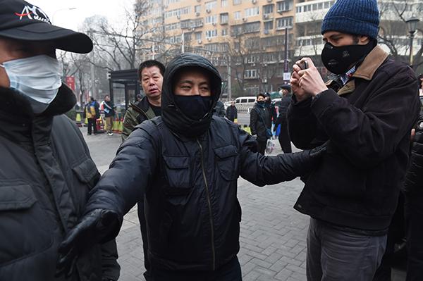 22 Aralık 2015 günü Pekin'de sivil polisler önde gelen bir insan hakları avukatının davası görülürken dışarıda bir gazeteci ile itişiyorlar. Çin'de insan hakları ihlallerini veya protesto gösterilerini belgeleyen gazeteciler hapis tehlikesiyle karşı karşıya. (AFP/Greg Baker)