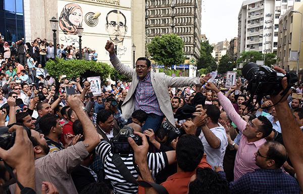 Mısır Gazeteciler Sendikası yönetim kurulu üyesi Khaled al-Balshy, güvenlik güçlerinin örgütlerinin Kahire merkez ofisine yönelik bir baskınını protesto edenlere katılırken. Mısır'ın basına baskı operasyonları dahilinde 25 gazeteci parmaklıklar ardında. (AFP/ Mohamed el-Shahed)