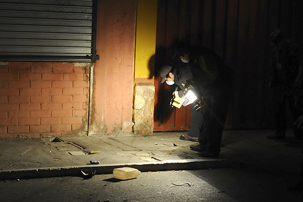 Officials inspect a crime scene in Guatemala City in 2013. High rates of street crime and violence make it hard to determine if victims are targeted for their work as journalists. (AFP/Johan Ordonez)