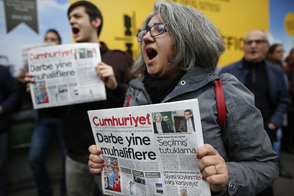 Türkiye'nin muhalif gazetesi Cumhuriyet'in destekçileri polis çok sayıda gazeteciyi gözaltına alırken İstanbul binasın dışında, protesto ediyorlar. (AP/Emrah Gürel)