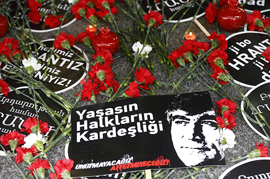 """On the 10th anniversary of his death, January 19, 2017, carnations, candles, and signs mark the spot in Istanbul where journalist Hrant Dink was murdered. The sign reads """"Long live the brotherhood of people. We will not forget, we will not forgive."""" (Reuters/Osman Orsal)"""