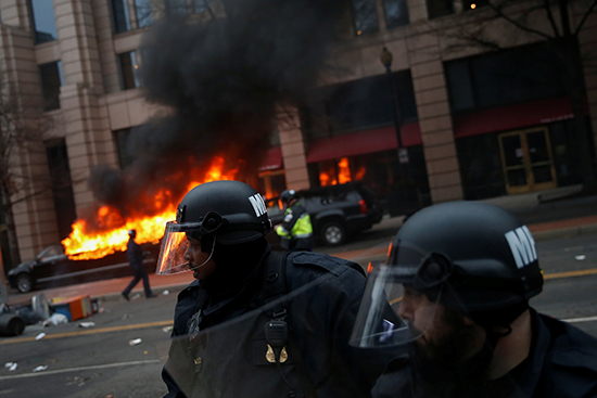 Police stand guard as a limousine set on fire by activists in Washington burns in the background, January 20, 2017. (Reuters/Adrees Latif)