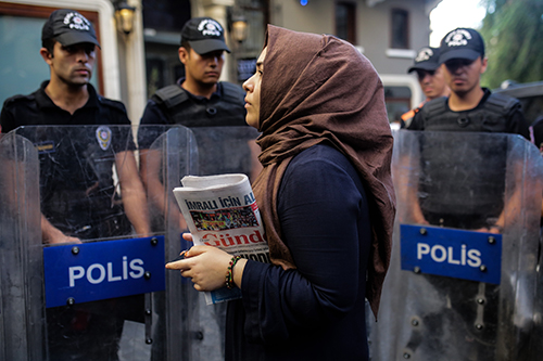 A woman holds a copy of Ozgur Gundem in front of a police barricade in August 2016. The publisher of the pro-Kurdish daily, which was ordered shut last year, has been detained. (AFP/Yasin Akgul)