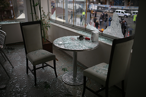 Broken glass scatters across the inside of a café close to the Izmir courthouse targeted in a bombing. News outlets have been ordered to report only official statements about the attack. (STR/AFP)