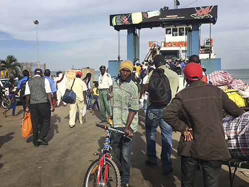 People board a ferry leaving Banjul in Gambia on January 18, amid the threat of military intervention after President Yahya Jammeh refused to concede defeat in elections. Gambia has denied entry to several journalists planning to cover the January 19 inauguration of Adama Barrow. (AP)