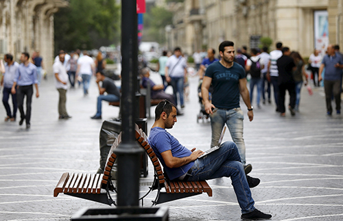 A man uses his laptop in a Baku street. Azerbaijan has extended its press freedom crackdown to include bloggers and social media users. (Reuters/Stoyan Nenov)