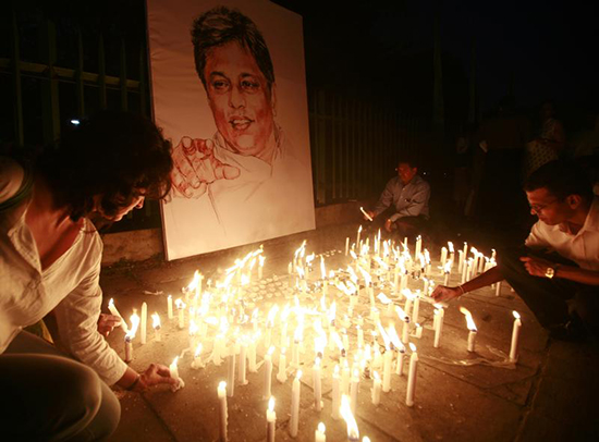 Media rights activists light candles in front of the portrait of slain Sri Lankan newspaper editor Lasantha Wickramatunga during a silent vigil to condemn his killing in Colombo, January 15, 2009. (Reuters/Buddhika Weerasinghe)