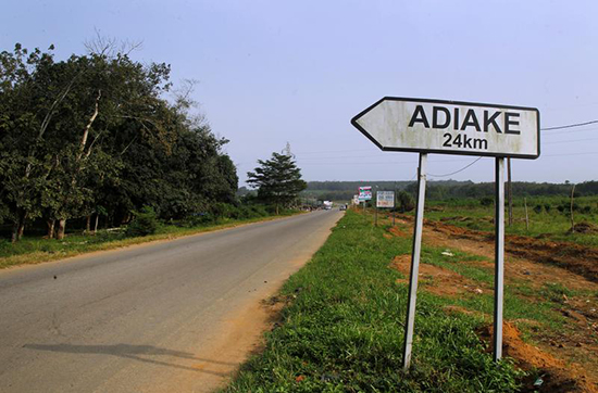 A sign for Adiake stands by an empty road in the Ivory Coast. Six journalists face charges of spreading false news for reporting on a settlement reached to end a military mutiny in the town. (Reuters/Luc Gnago)