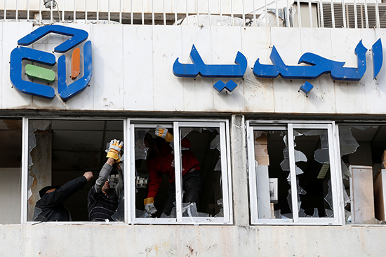 Workers remove broken glass from the windows of broadcaster Al-Jadeed's office in Beirut, February 15, 2017. Some 300 people attacked the building the previous night. (Reuters/Mohamed Azakir)