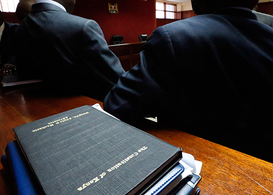 Lawyers confer on the floor of Kenya's High Court in Nairobi, next to a copy of the country's constitution, March 8, 2013. (Reuters/Steve Crisp)