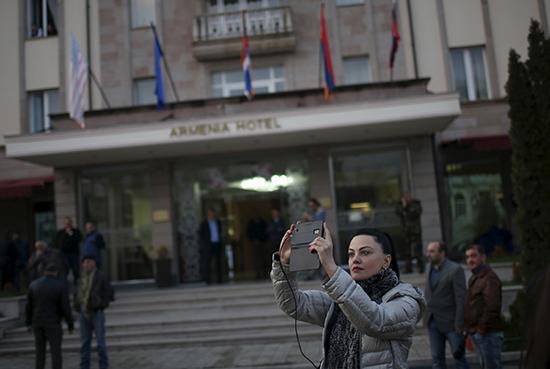 A woman takes a photograph in Stepanakert, Nagorno-Karabakh, April 7, 2016. (Reuters)