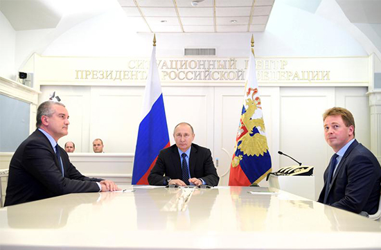 Russian President Vladimir Putin (center), head of Crimea Sergei Aksyonov (left), and then-Sevastopol Acting Governor Dmitry Ovsyannikov, take part in a video conference in Moscow, December 27, 2016. (Sputnik/Alexei Druzhinin/Kremlin via Reuters)