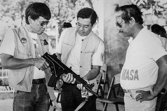 Philippine President Rodrigo Duterte (left), then mayor of Davao, inspects an assault rifle with Regional Police Chief Miguel Abaya (center) in the late 1980s. (Reuters/Renato Lumawag)