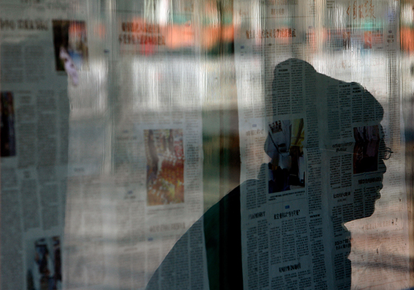 A passerby reads newspapers posted on a bulletin board in Beijing. Some foreign correspondents in China say they are finding it hard to find citizens willing to be interviewed. (AFP/Teh Eng Koon)