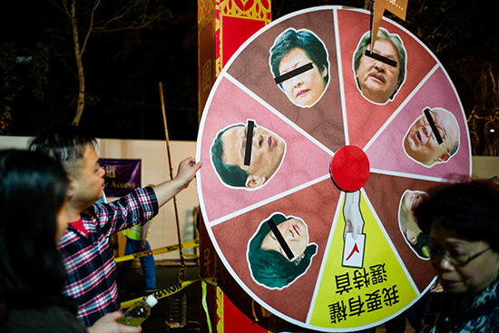 A man spins a wheel during new year festivities to predict the winner of Hong Kong's chief executive election. The daily Sing Pao says its staff are being harassed because of its critical coverage. (AFP/Anthony Wallace)