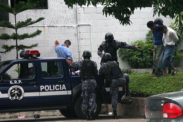 Police escort detainees to a court hearing in 2009 over the killing of freelancer Christian Poveda in El Salvador. Safety training is essential for journalists covering dangerous beats in Central America. (AP/Edgar Romero)