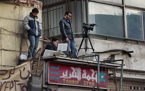 Journalists transmit footage of protests in Egypt's Tahrir Square in February 2011. Advances in technology that bring reporters closer to the action increase the dangers they face. (AP/Ben Curtis)