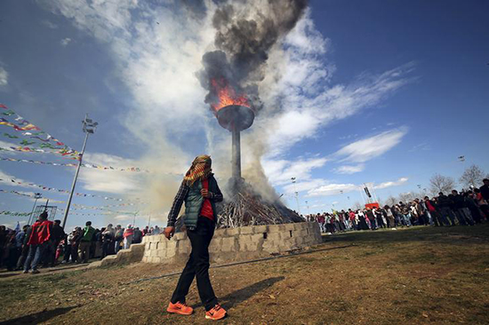 A demonstrator walks around a bonfire to mark the spring festival of Newroz in the southeastern Turkish city of Diyarbakır, March 21, 2016. Ethnic Kurds marked the occasion last year with a demonstration calling for the resumption of peace talks with the government. (Reuters/Sertac Kayar)