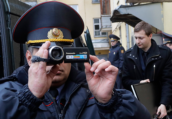 A Belarusian Interior Ministry official films journalists reporting on a police raid of one of Belsat TV's offices in Minsk, March 31, 2017. (AP/Sergei Grits)