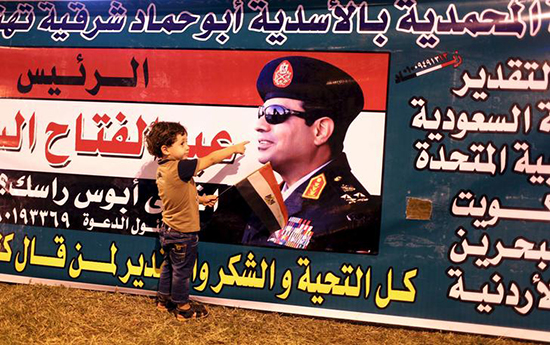 A child poses for a picture with a poster of Egyptian President Abdel Fattah el-Sisi in Cairo, August 6, 2015, as supporters cheered improvements to the Suez Canal.