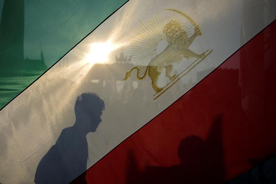 An activist holds an Iranian flag in a protest in Berlin, September 3, 2016. (Reuters/Stefanie Loos)
