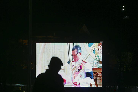A military officer watches a television screen showing Thailand's King Maha Vajiralongkorn Bodindradebayavarangkun speaking after he accepted an invitation from parliament to succeed his late father at the Dusit Palace in Bangkok, Thailand, December 1, 2016. (Reuters/Athit Perawongmetha)