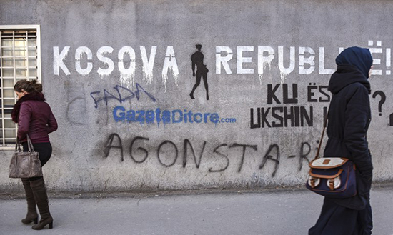 Women walk by graffiti reading Kosovo Republic in Pristina, February 13, 2017. (AFP/Armend Nimani)