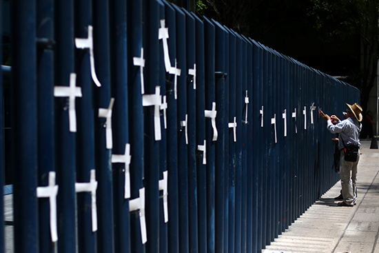 A man attaches crosses to the fence of the attorney general's office (PGR) in Mexico City to protest the murder of journalists, April 1, 2017. (Reuters/Edgard Garrido)
