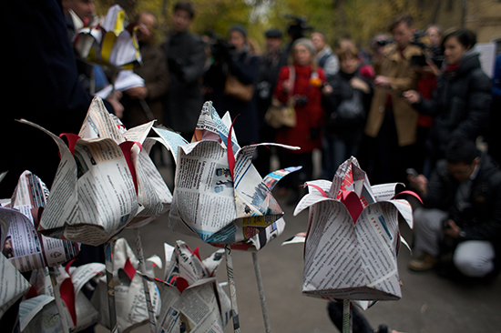 People lay flowers made of newspapers to pay respects to slain Novaya Gazeta journalist Anna Politkovskaya outside the newspaper's office in Moscow, October 7, 2014. (AP/Ivan Sekretarev)