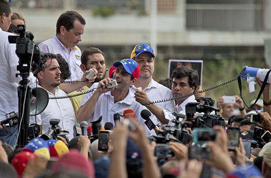 Opposition leader Henrique Capriles addresses protesters and the press in Caracas on April 22. Journalists and news outlets covering the unrest have been harassed. (AP/Fernando Llano)