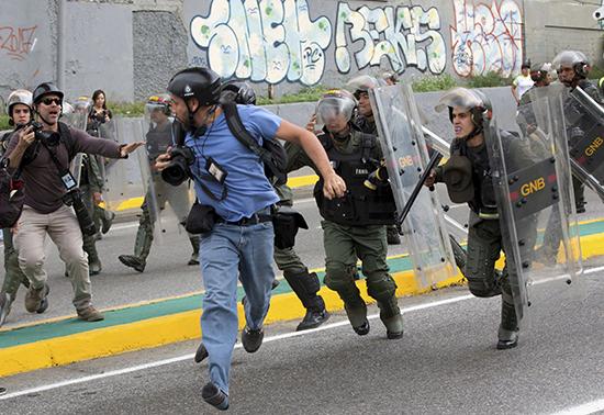 Um fotojornalista da Reuters corre enquanto efetivos da Guarda Nacional Bolivariana avançam durante um protesto em frente ao Tribunal Supremo de Justiça em Caracas, em 31 de março. Vários jornalistas foram feridos cobrindo os distúrbios. (AP/Ariana Cubillos)
