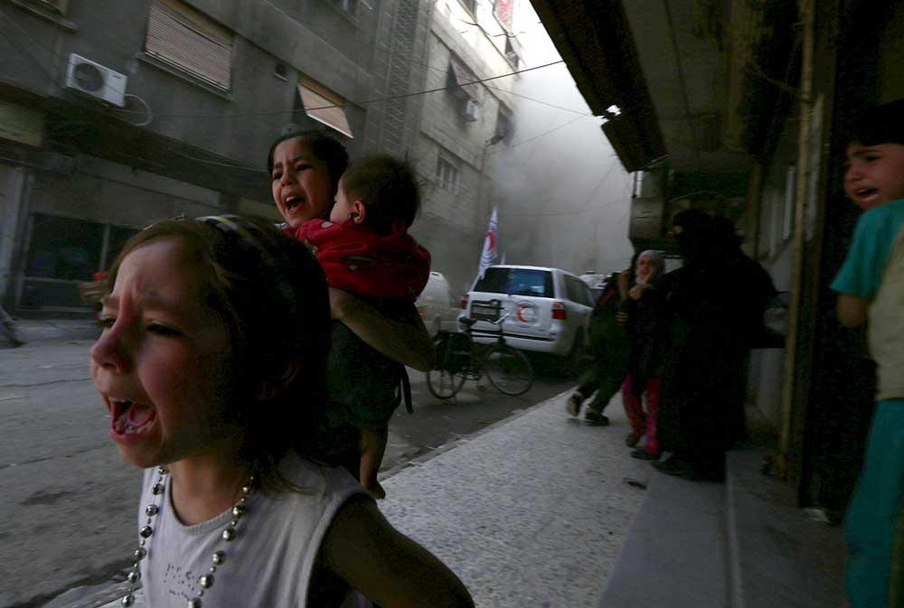 أطفال سوريون يصرخون في أعقاب ما وصفه ناشطون بأنه قصف شنته قوات موالية للرئيس بشار الأسد بالقرب من مركز للهلال الأحمر السوري في دمشق في 5 مايو/ أيار 2015. (رويترز/ بسام خابية)