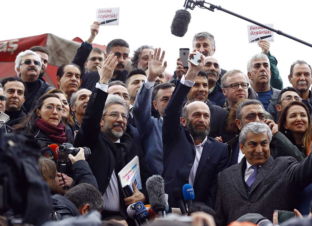 Can Dündar, then editor-in-chief of Cumhuriyet, center left, and Ankara bureau chief Erdem Gül greet supporters as they arrive for a court hearing in Istanbul in March 2016. (Reuters/Osman Orsal)