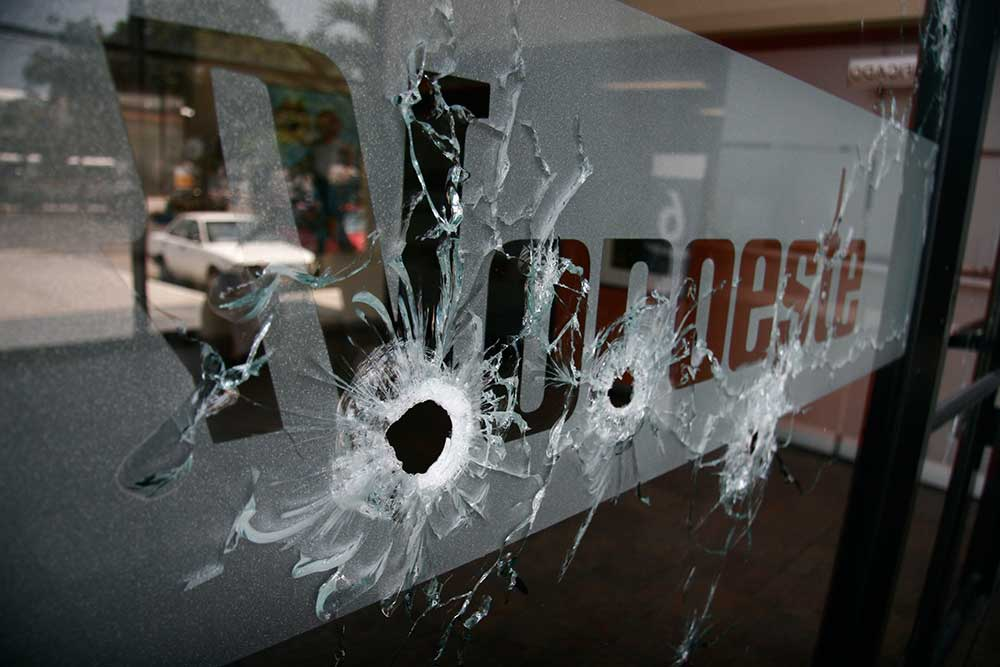 The entrance to Noroeste is covered with bullet holes after gunmen opened fire on the newspaper's regional office in the Pacific resort city of Mazatlán, Mexico, on September 1, 2010. (AP/Christiann Davis)
