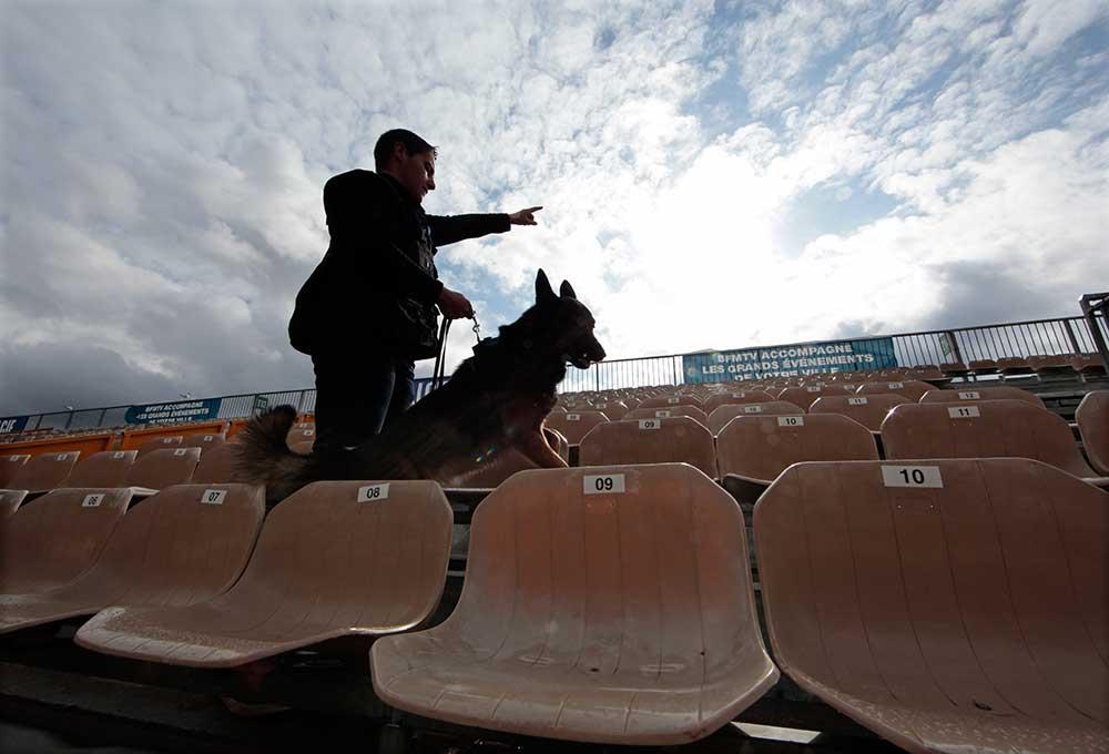 Офицер французской полиции использует собаку-ищейку при проверке стадиона в Ницце в феврале 2016 года. Европейские города усилили меры безопасности после серии террористических атак. (Рейтер/Эрик Гайяр)