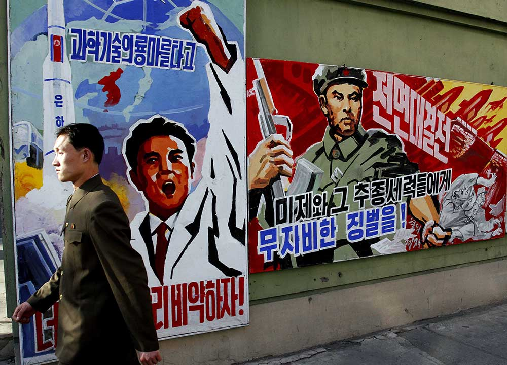 A North Korean man walks past propaganda posters in Pyongyang, North Korea, that threaten punishment to the 'U.S. imperialists and their allies.' (AP/Kim Kwang Hyon)