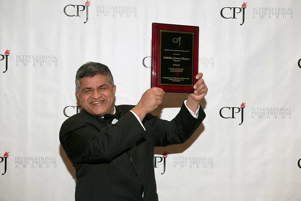 Political cartoonist Zunar, shown accepting CPJ's International Press Freedom Award in 2015, faces the possibility of dozens of years in prison as a result of his cartoons attacking Malaysian Prime Minister Najib Razak. (CPJ)