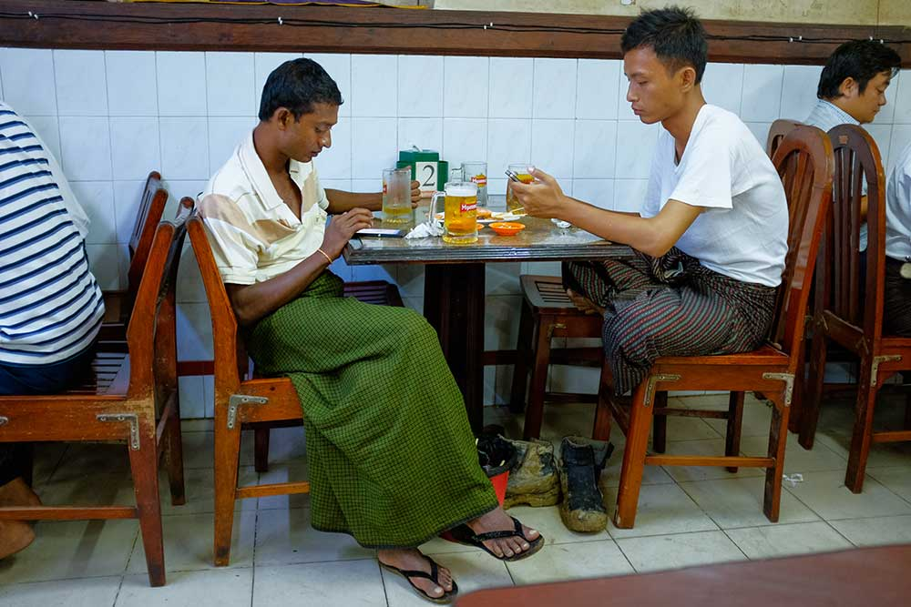 Young men check their Facebook pages at a restaurant in Yangon, Myanmar, over beers and dinner. The social network is improving access to news in remote areas. (Jerry Redfern)