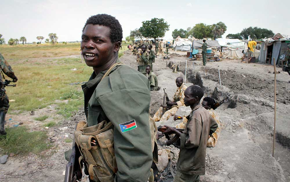 South Sudanese government soldiers stand in trenches in Malakal in October 2016. The army flew in journalists to show that they retain control of the city, which has been reduced to rubble and almost entirely deserted by civilians. (AP/Justin Lynch)