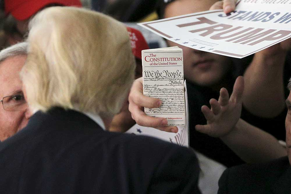 Nisan 2016'da, Donald Trump'ın Rhode Adası mitinginde kalabalıktan biri ABD Anayasası'nı gösteriyor. (Reuters/Brian Snyder)
