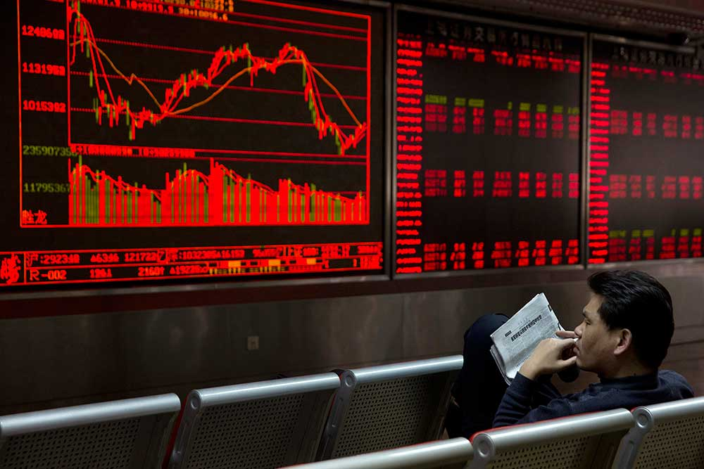 Un investisseur chinois suit l'évolution des cours boursiers dans une société de courtage à Beijing en février 2016. Les autorités ont annoncé qu'elles prévoyaient de noter «la crédibilité sociale» des individus. (AP/Ng Han Guan)