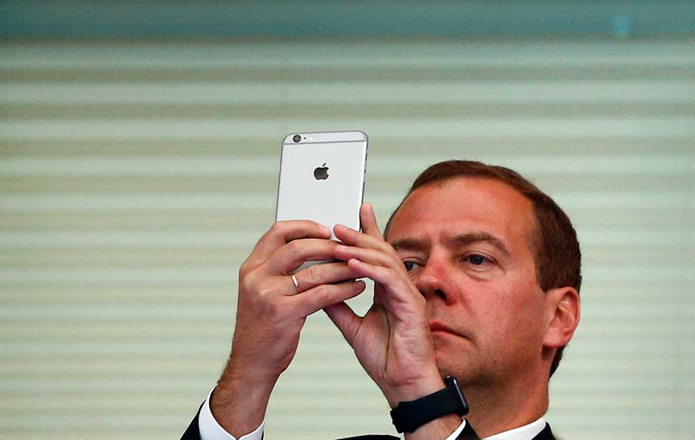 Russian Prime Minister Dmitry Medvedev uses a smartphone at the Aquatics World Championships in Kazan, Russia, in August 2015. Moscow is trying to bring the internet under its control. (Reuters/Hannibal Hanschke)