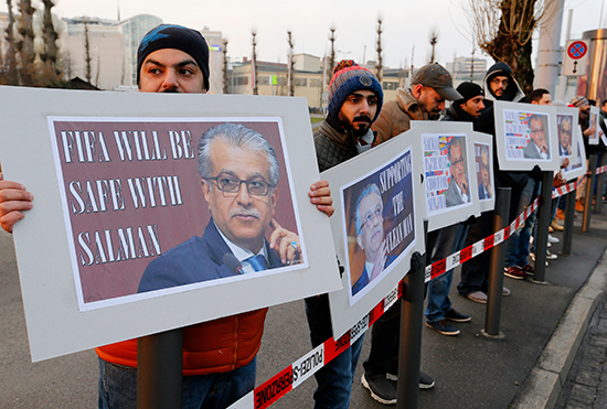 "Supporters of Bahraini Sheikh Salman bin Ebrahim Al-Khalifa hold signs reading ""Supporting the clean man"" and ""FIFA will be safe with Salman"" in Zurich, Switzerland, February 26, 2016. (AP/Michael Probst)"