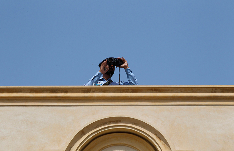 A security official looks through binoculars from the roof of the High Court in Islamabad, April 12, 2013 (Reuters/Milan Kursheed)
