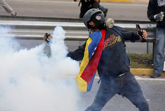 Um manifestante lança uma lata de gás lacrimogêneo de volta à polícia em Caracas, 2 de maio de 2017. (Reuters / Carlos Garcia Rawlins)