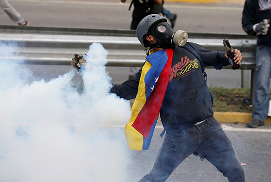 A protester throws a tear gas canister back at police in Caracas, May 2, 2017. (Reuters/Carlos Garcia Rawlins)