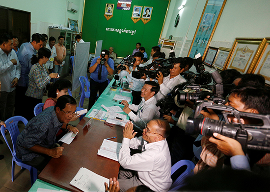 Journalists crowd around Cambodian Prime Minister Hun Sen in the province of Kandal, September 1, 2016, as he registers to vote in local elections scheduled for June 4, 2017. (Reuters/Samrang Pring)