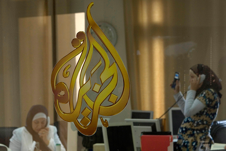 In this 2009 file photo, Palestinian journalists work in the Ramallah office of Qatari broadcaster Al-Jazeera. Saudi Arabia, the United Arab Emirates, and Bahrain blocked access to Al-Jazeera's websites on May 24, 2017. (Reuters/Fadi Arouri)