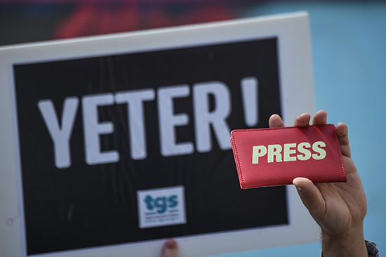 A journalist holds a press sign next to a placard reading 'Enough!' during a World Press Freedom Day rally in Istanbul. Turkey is a leading jailer of journalists. (AFP/Ozan Kose)